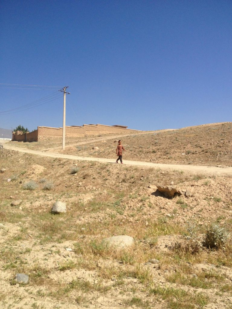 Mały chłopiec idący górskim zboczem nad jeziorem Qargha