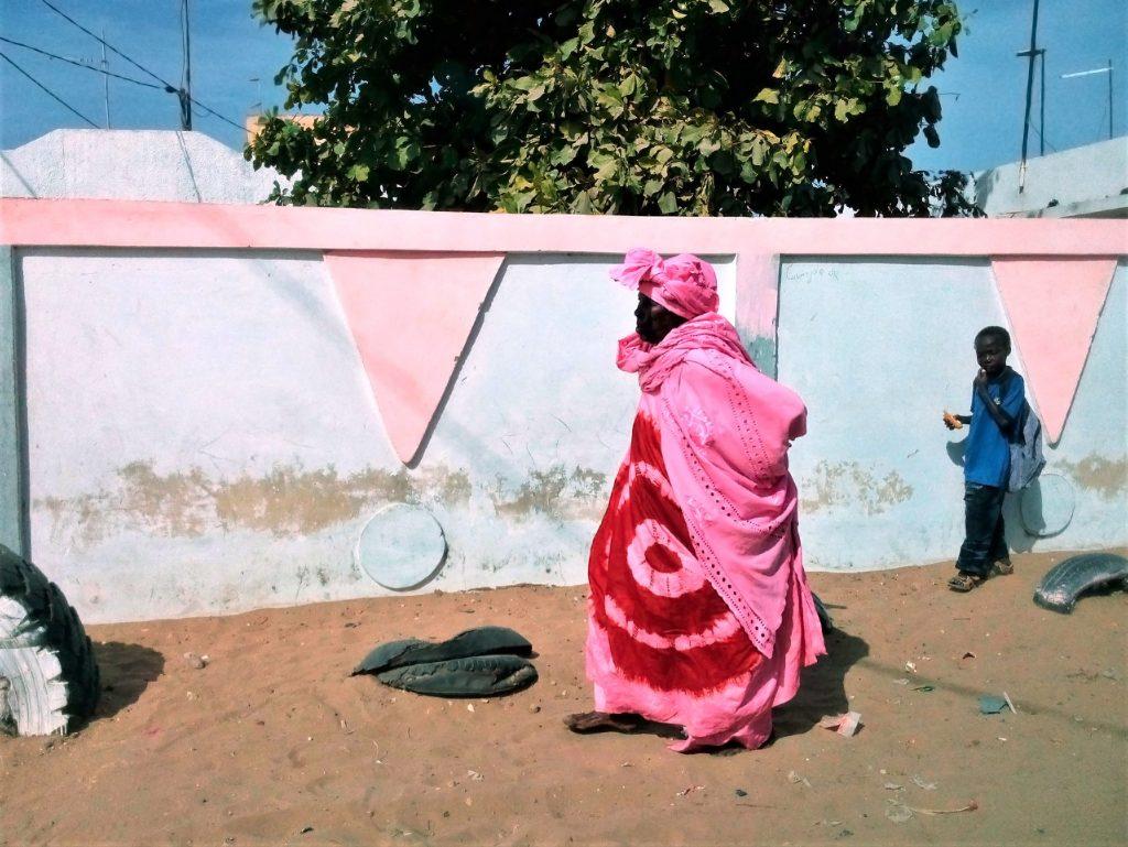 Kobieta idąca poboczem, po drodze prowadzącej do czerwonego jeziora niedaleko Dakaru