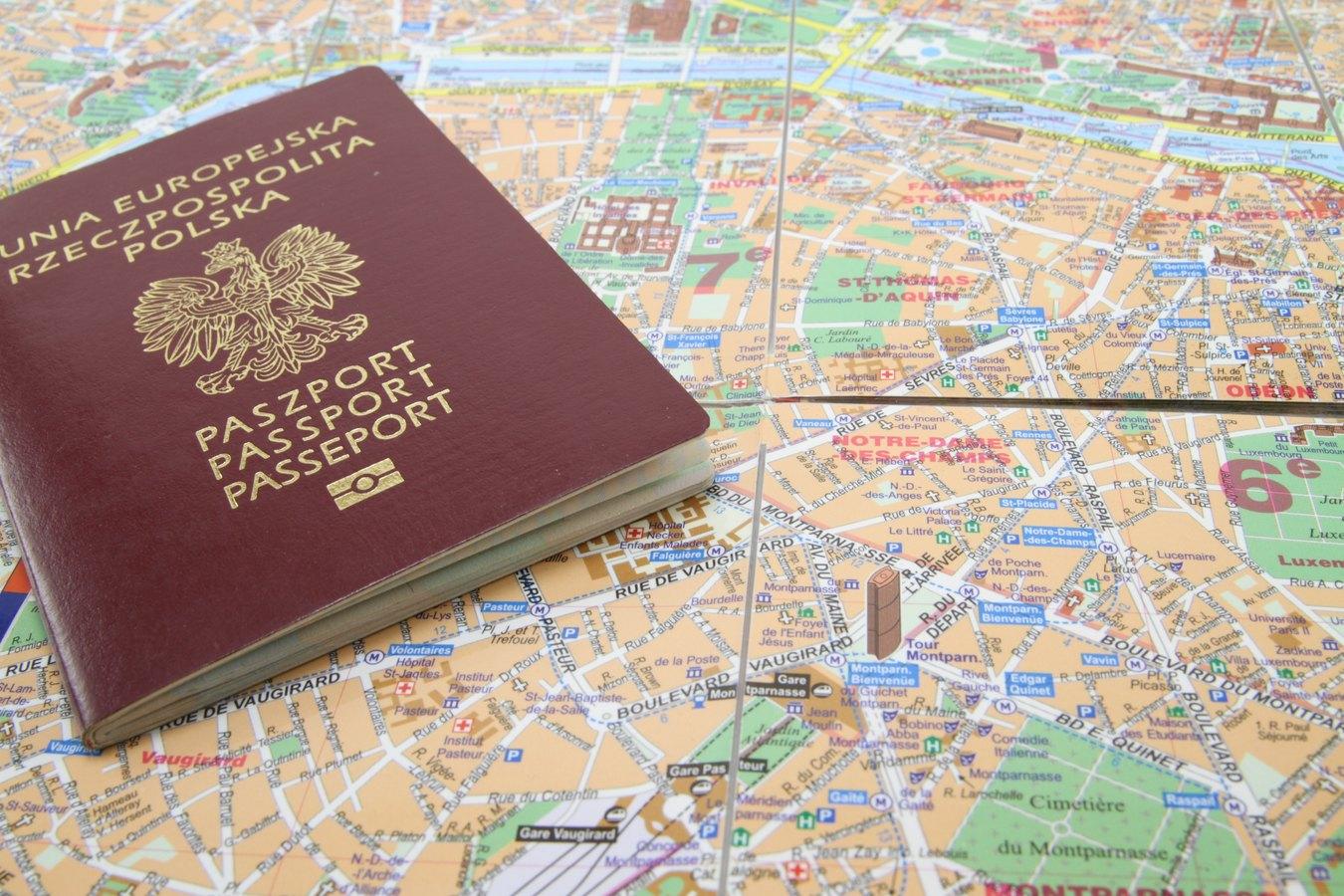 Polski paszport na tle mapy Paryża