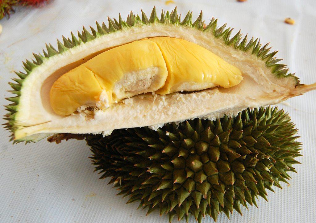 Przekrojony durian z widocznym fragmentem miąższu