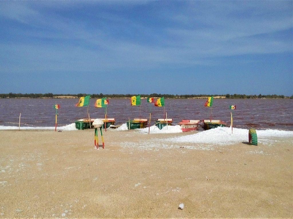 Łodzie i flagi Senegalu nad brzegiem czerwonego jeziora