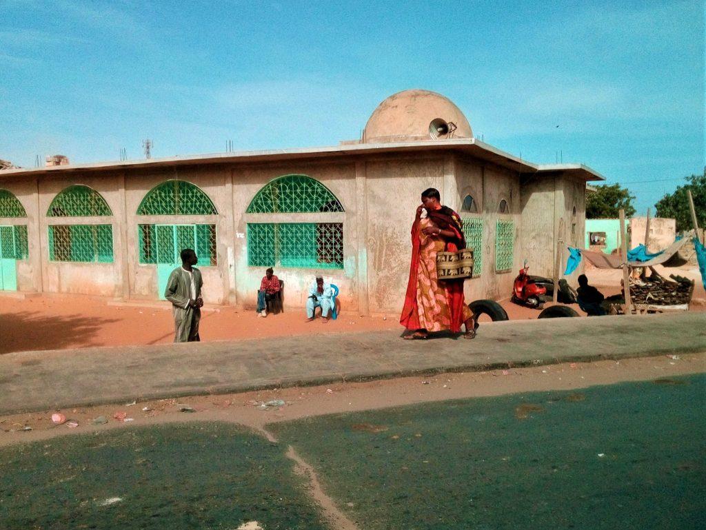 Tradycyjnie ubrana kobieta na tle meczetu idzie drogą prowadzącą do Czerwonego Jeziora