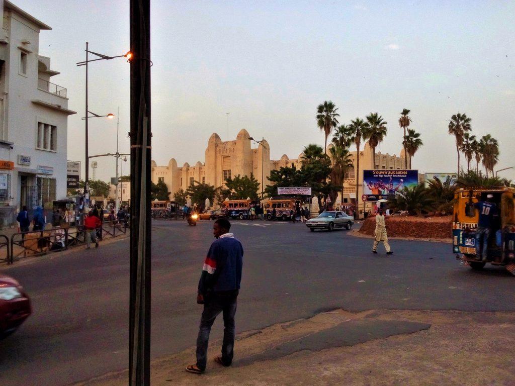 Ulica w Dakarze w Senegalu a w tle budynek łączący elementy modernizmu i tradycyjnej lokalnej architektury