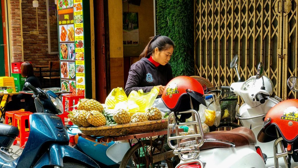 Sprzedawczyni ananasów przygotowuje towar na ulicy w Hanoi