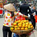 Sprzedawczyni pomarańczy prowadzi rower przez ulice Hanoi na głowie mając tradycyjny kapelusz